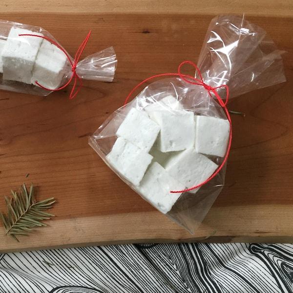 Des cubes de guimauve dans un petit sac et des branches de sapin sur une planche de bois.