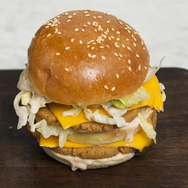 Deux hamburgers doubles végé servis sur une planche de bois.