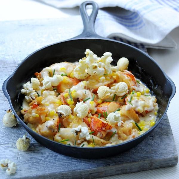 Un mélange de homard crémeux, maïs et maïs soufflé dans un contenant noir.