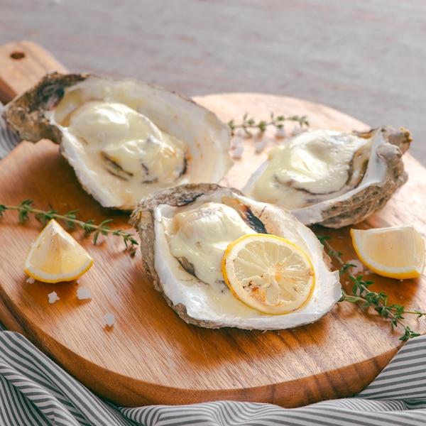 Trois huîtres à la monarde sur une planche de service.