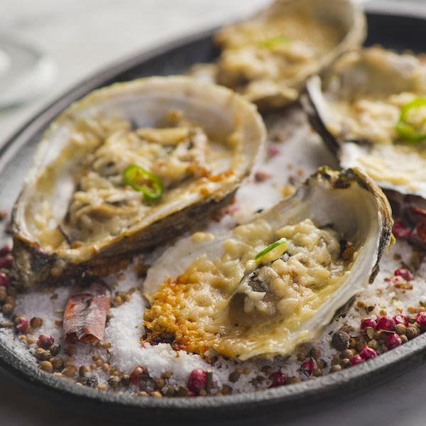 Quatre huîtres bien garnies déposées dans un bol rempli de sel.