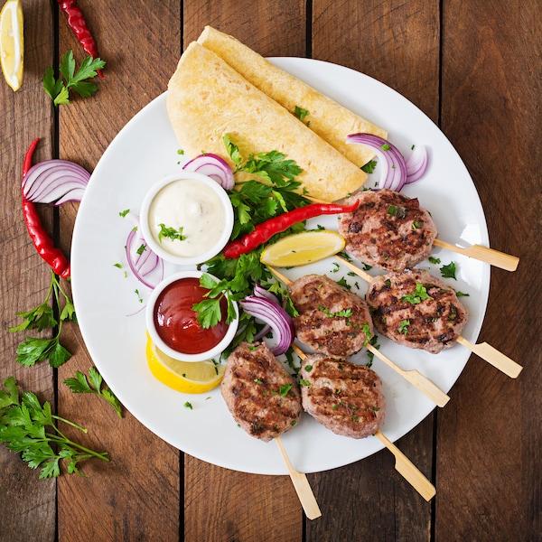 Quatre brochettes de kefta dans une assiette avec des tortillas, des légumes et deux bols de sauce.