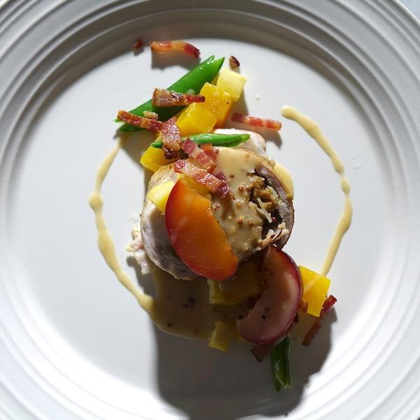 Un morceau de lapin rôti accompagné de prunes marinées et de quelques légumes et fruits.
