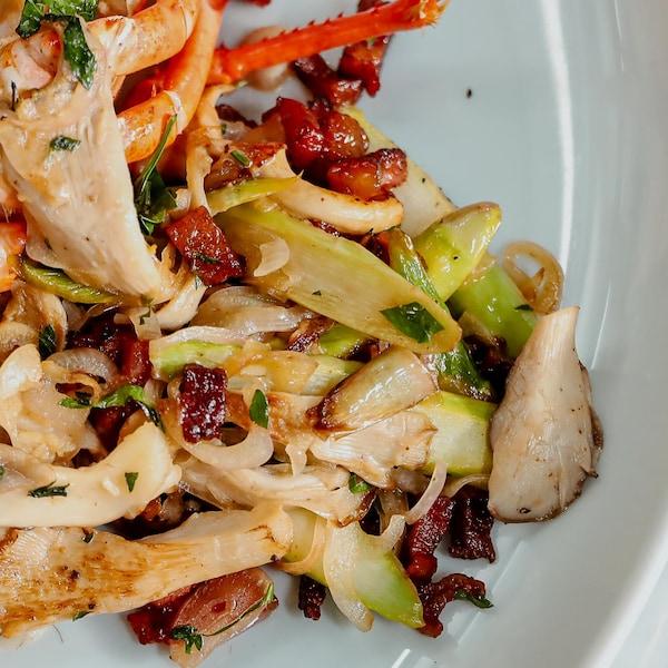 Des légumes poêlés aux lardons dans un plat de service.