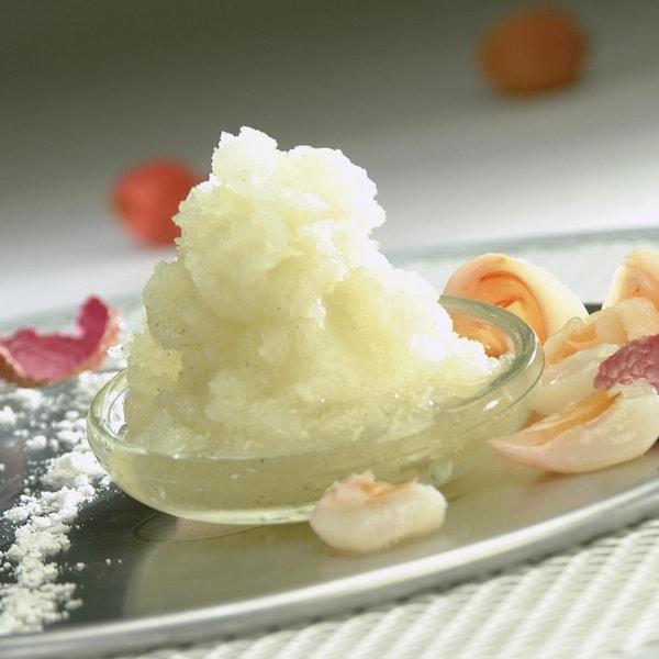 Le granité de citron vert à la vanille est dans une petite soucoupe transparente entourée de litchis marinés.