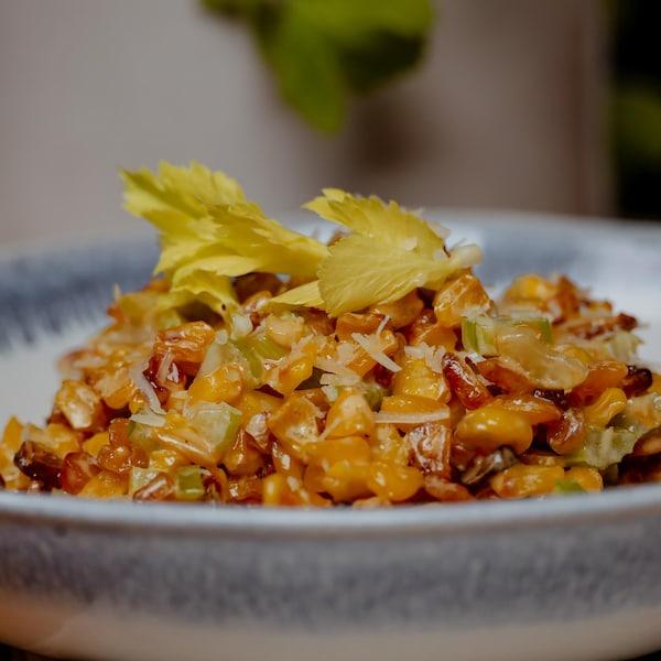Un bol de maïs à la crème garni de feuilles de céleri.