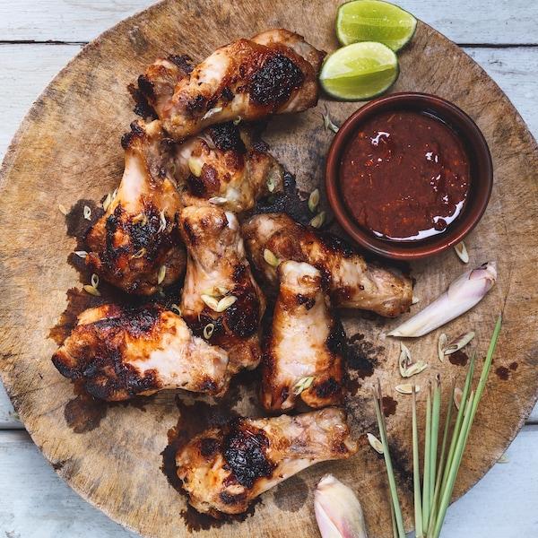 Des ailes de poulet grillées avec un bol de sauce et des quartiers de lime sur une plaque en bois.