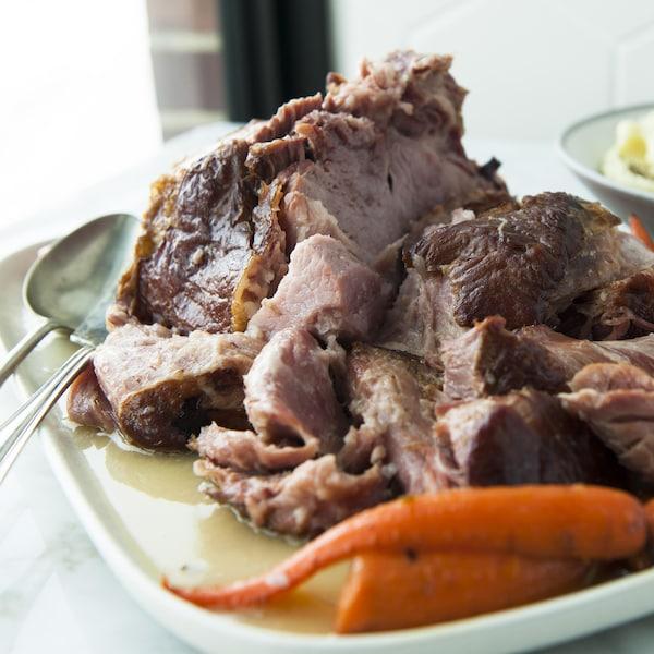 Un jambon en tranches dans un plat de service, avec des carottes et de la purée de pommes de terre.