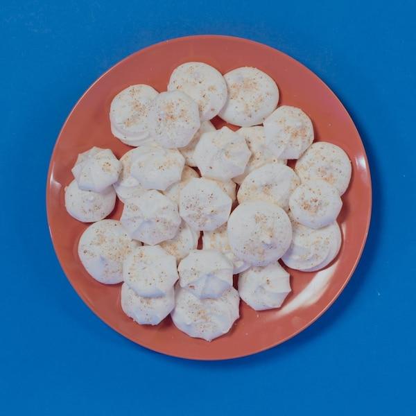 Des meringues dans une assiette rouge sur fond bleu.