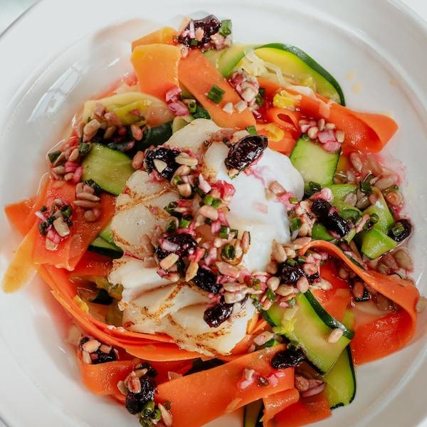 Un pavé de morue grillé garnis de ruban de légumes et nappé de sauce à la camerise