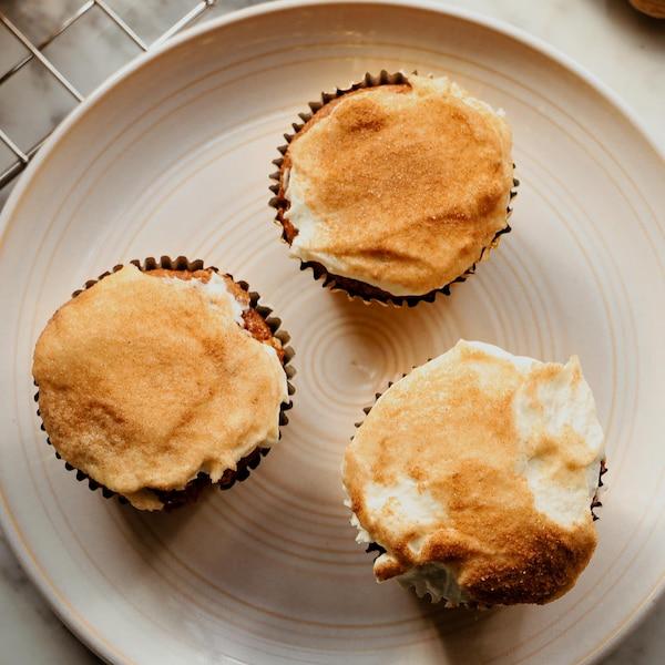 Des muffins glacés et saupoudrés de mélange de sucre et de cannelle, servis dans une assiette.