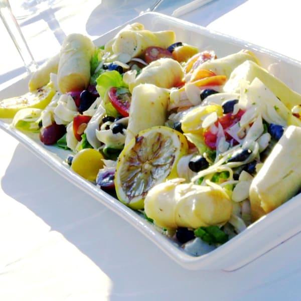 Un plat rempli de nems et de légumes divers.
