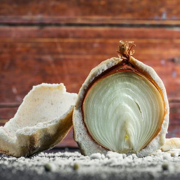 Un oignon en croûte de sel tranché en deux.