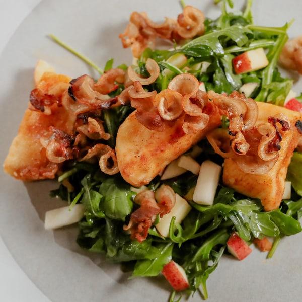Une assiette de salade de roquette, garnie de cubes de fromage grillés et de d'oreilles de crisse.