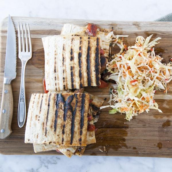 Deux parts de panini servies sur une planche de bois avec des ustensiles et accompagnées de salade de chou.