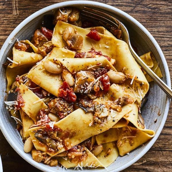Deux bols de pâtes fraîches à la saucisse italienne et aux haricots blancs posés sur une surface en bois.