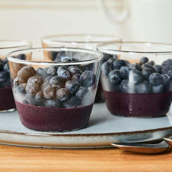 Sur une assiette, est déposé quatre petits pots en verre, contenant la recette de choco-bleuets glacés au fond et des bleuets frais sur le dessus.
