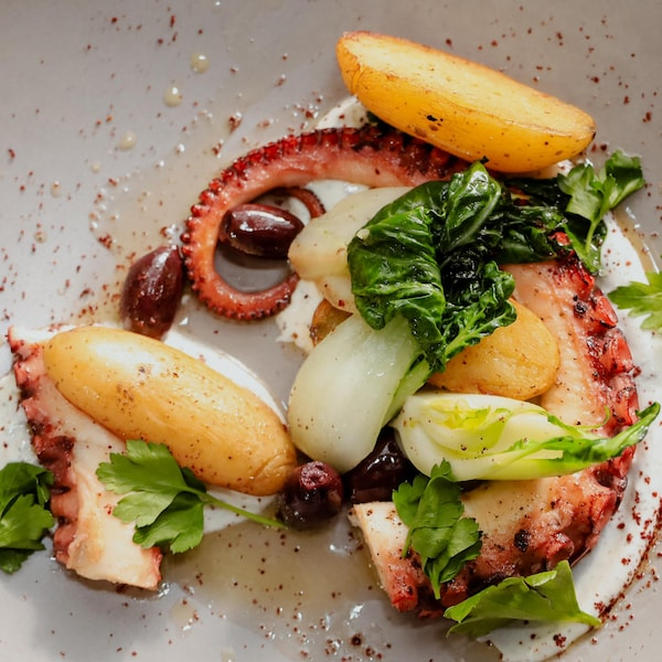De la pieuvre grillée servie avec des pommes de terre rattes aux olives et de la verdure.