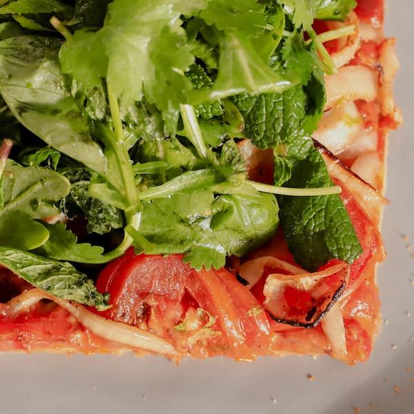 Un carré de pizza au beurre d'arachides garni de salade au pesto aux herbes.