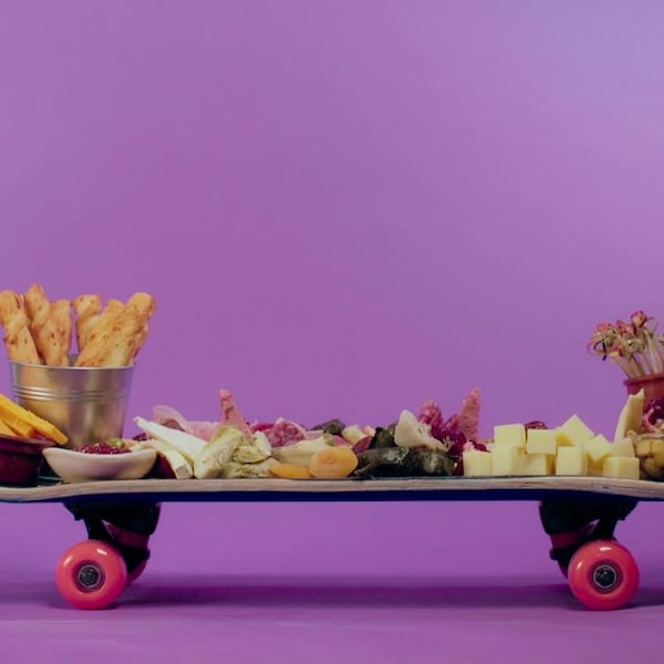 Une planche à roulettes qui sert d'ardoise pour l'apéro. S'y retrouvent: des fromages variés, des charcuteries, des marinades, des croûtons et des fruits et légumes.
