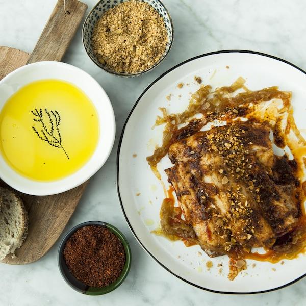Une assiette de poisson rôti servi avec du pain et des condiments.
