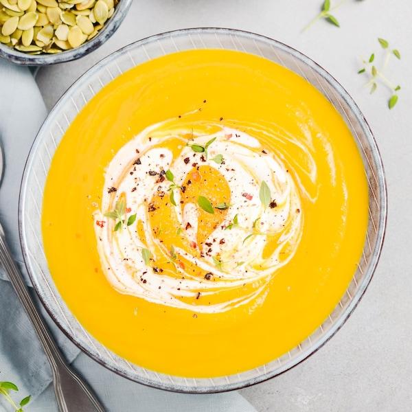 Un potage à la courge décoré de pousses et de crème.
