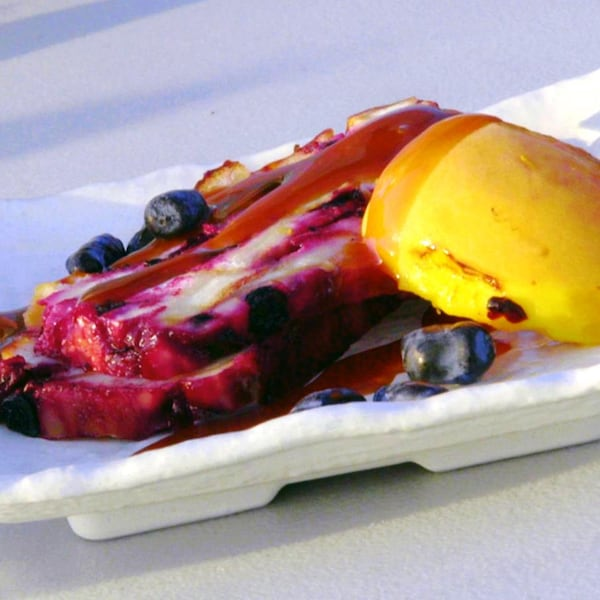 Un morceau de pouding chômeur dans une assiette avec des camerises.
