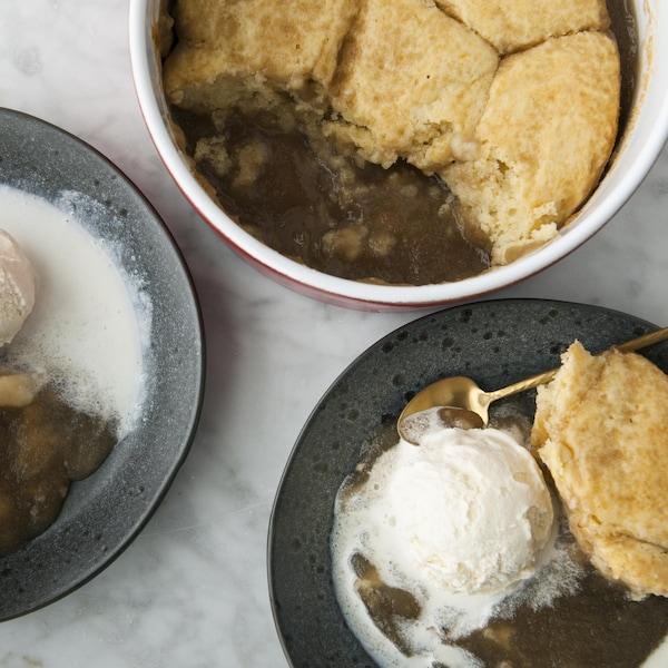 Des parts de pouding chômeur servies avec de la crème glacée à la vanille.