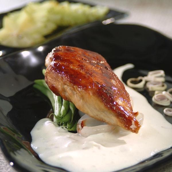 Un morceau de poulet sur une bonne quantité de sauce blanche dans une assiette noire.
