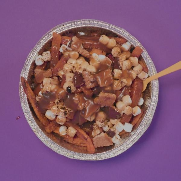 Un plat pour emporter rempli de poutine dessert, composée de frites de patate douce, de guimauves et de biscuits émiettés.
