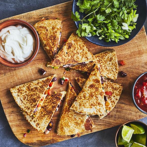 Portions de quesadillas sur une planche en bois avec un bol de salsa et de crème sure.