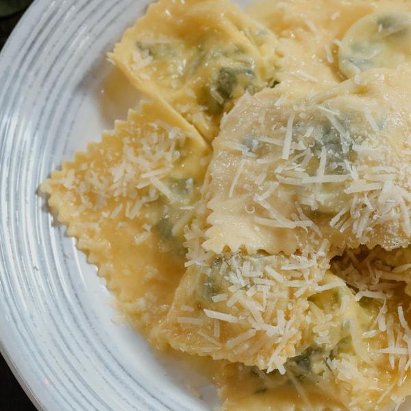 Une assiette de raviolis farci à la ricotta et aux épinards, garnis de parmesan fraîchement râpé.