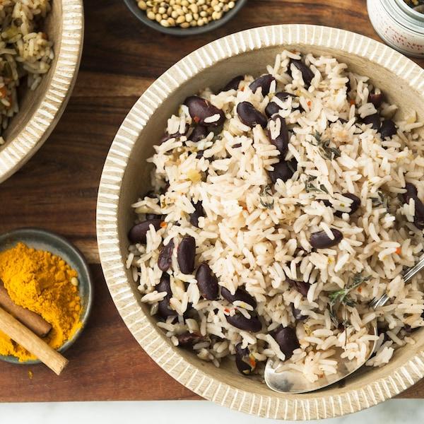Un bol de riz collé entouré de petits pot d'épices et d'un plat de riz créole à la mangue.