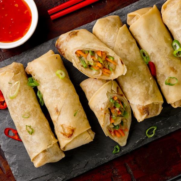 Sept rouleaux impériaux dans une assiette accompagnés d'une sauce orangée.