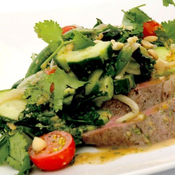 Des morceaux de bœuf avec de la salade par-dessus.