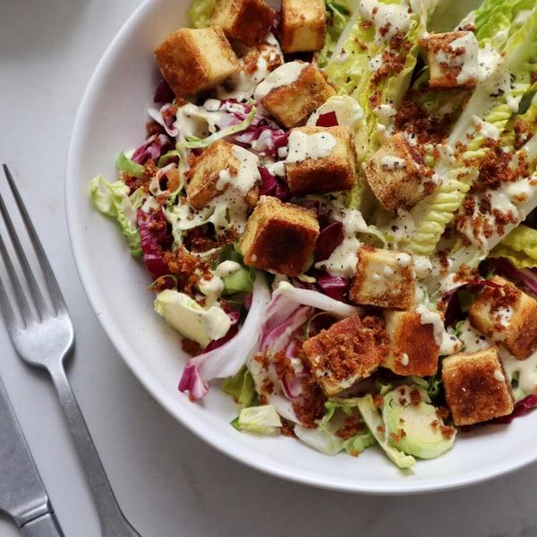 Un bol de salade César végane, garnie de croûtons de tofu.