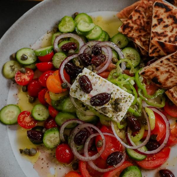 Une salade grecque composée d'olives, de tomates, de concombres et de poivrons, garnie de feta, d'olives et de câpres.