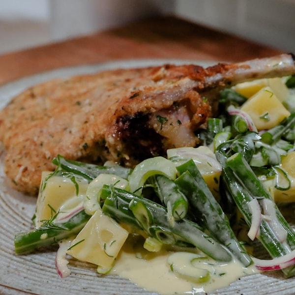 Une assiette comprenant de la salade de haricots et de pommes de terre, servie aux côtés de côtelettes à la milanaise.