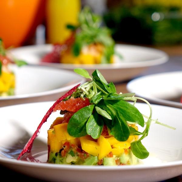 Une salade de homard, d'avocat et de mangues déposée en cercle dans une assiette.