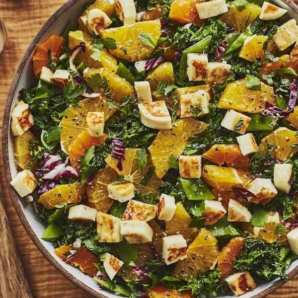 Un grand bol de salade de kale garni de suprêmes d'orange et de halloumi.