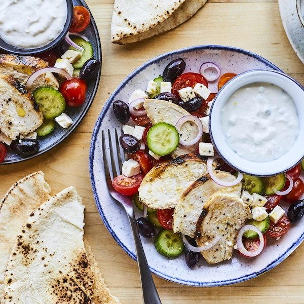 Plusieurs assiettes de salades de poulet grillé à la grecque sur une table avec des pains pitas.