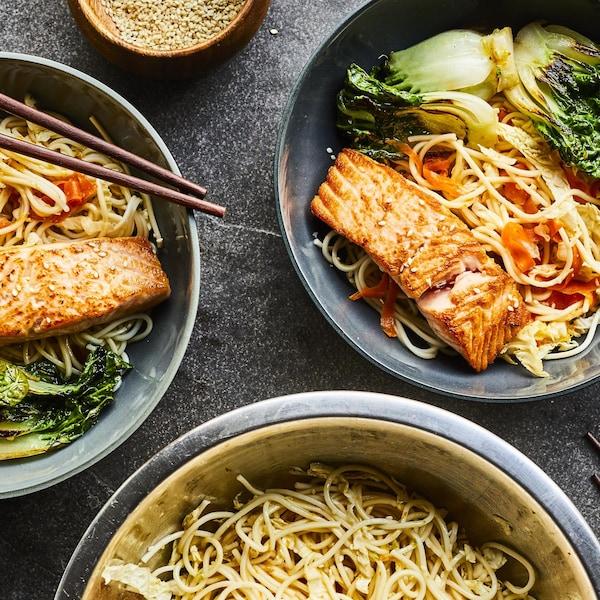 Bols de nouilles asiatiques avec morceaux de saumon, bok choys et des baguettes, sur une table en béton.