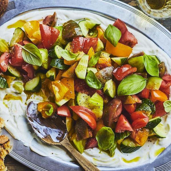 Salade de tomates à la ricotta fouettée dans une grande assiette de service.