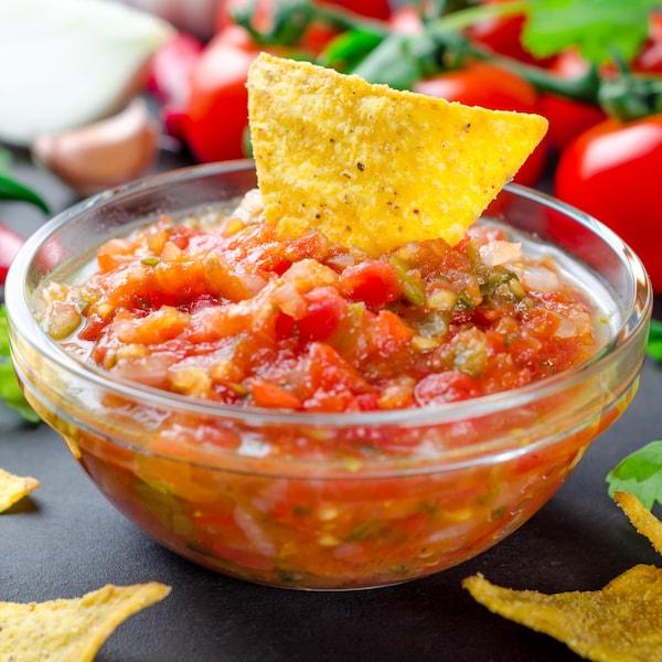 Un bol de salsa fraîche avec une croustille trempée dedans.