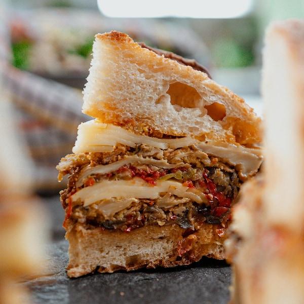 Une portion de sandwich végératien de style muffuletta.