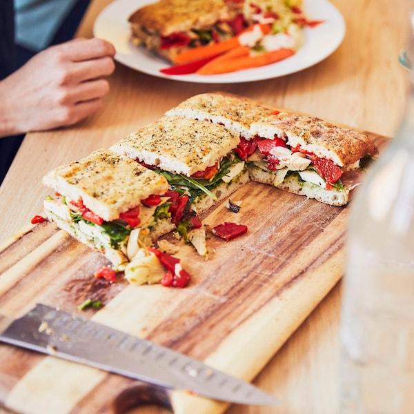 Gros sandwich à partager posé sur une planche de bois.