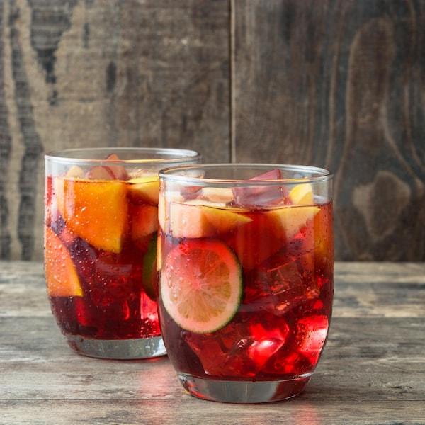 Deux verres de sangria sur une table en bois.