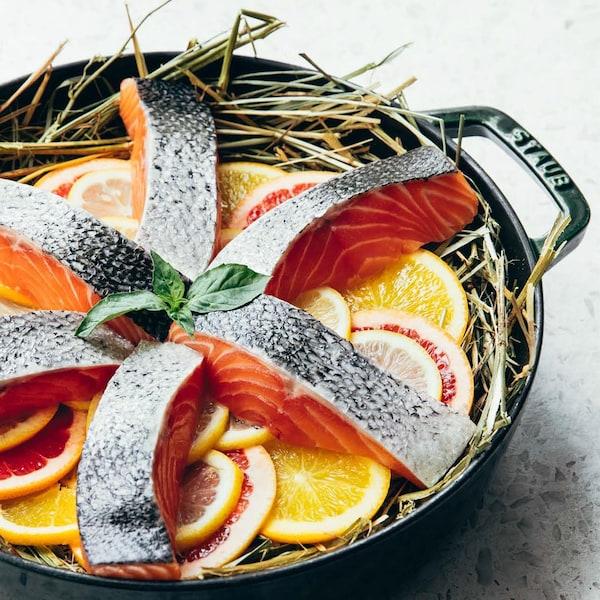 Une casserole avec des filets de saumon sur un lit de tranches d'agrumes et de foin.