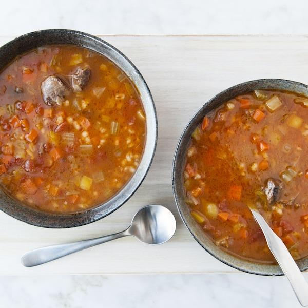 Des bols de soupe au boeuf et à l'orge servis sur une planche de bois, avec des cuillères à soupe.