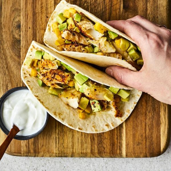 Deux tacos de poisson sur une table.